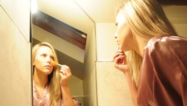 A girl touching up her makeup in a steam-free bathroom mirror